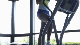 Young woman using exercise machine, low section (blurred motion)