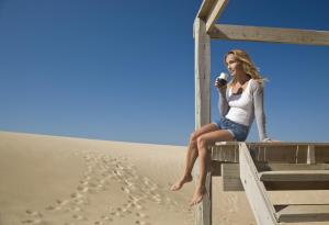 Woman holding mate cup on stairs of beach house, sand dunes in background