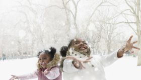 Mixed race girls catching snowflakes