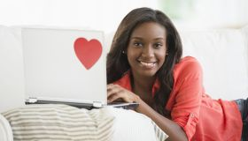 Black woman using laptop on sofa