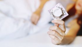 Midsection Of Woman Holding Condom While Lying On Bed