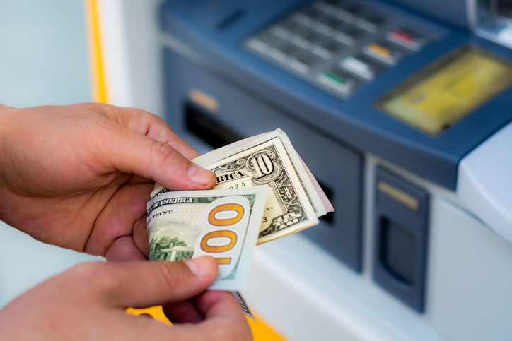 Cropped Hands Of Person Removing Cash From Atm Machine