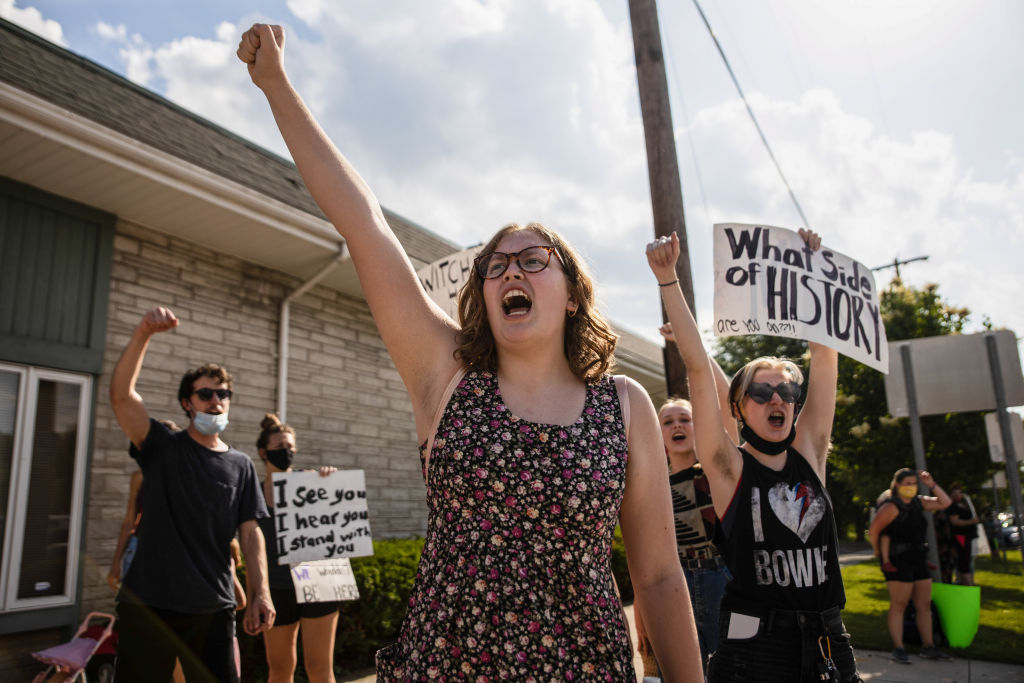 Young protesters hold up their fists during a peaceful...